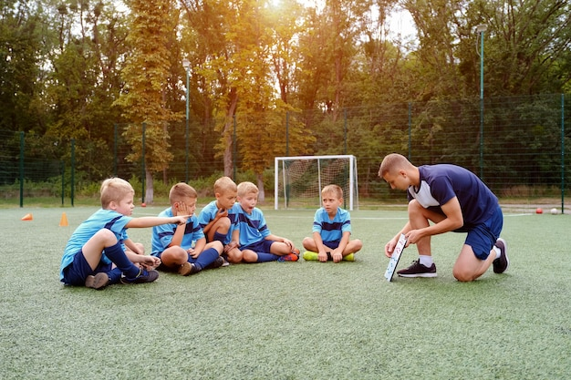 Young coach with clipboard teaches kids strategy of playing on football field.