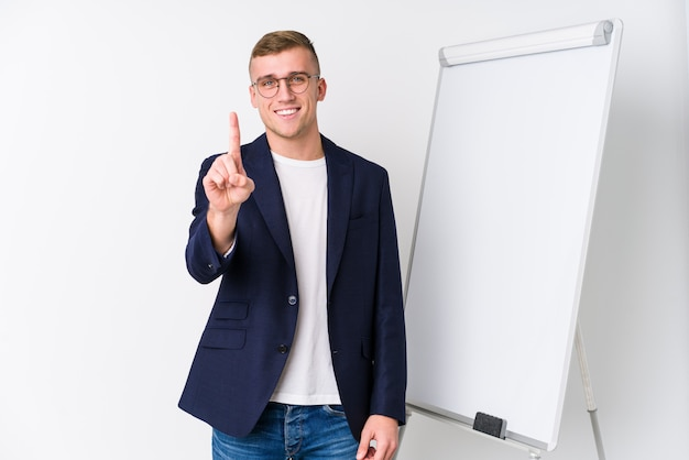 Young coaching man showing a white board showing number one with finger.