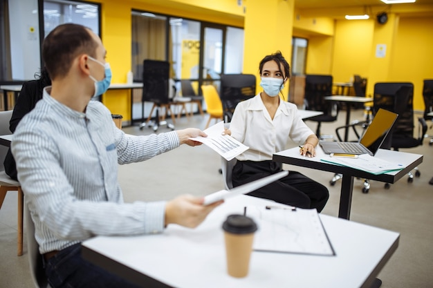Young colleagues pass documents to each other working at an office during coronavuris pandemic outbreak.