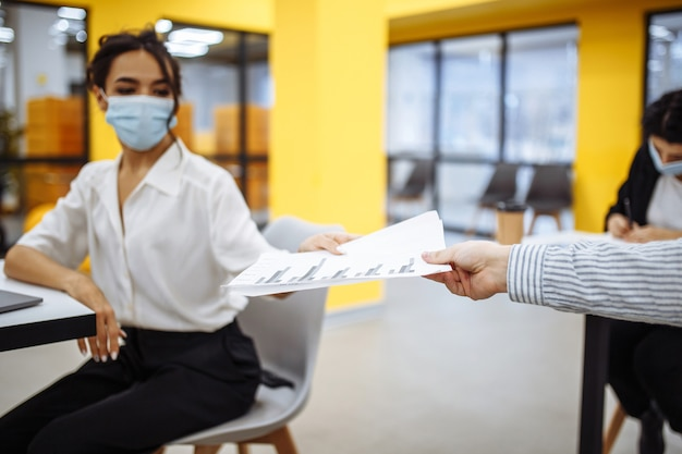 젊은 동료들은 코로나 뷰리스 전염병이 발생하는 동안 사무실에서 일하는 문서를 서로에게 전달합니다.