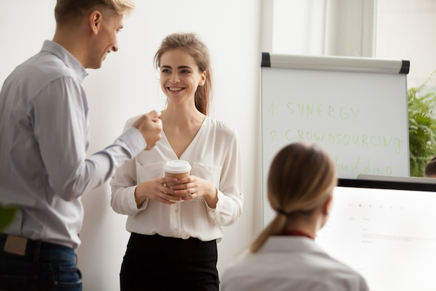 Young colleagues talking laughing at coffee break in coworking office