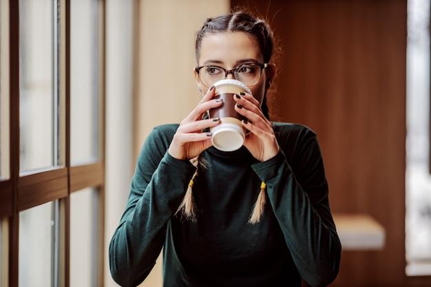 Молодая девушка колледжа сидит в кафе возле окна и пьет свежий кофе из одноразовой чашки.