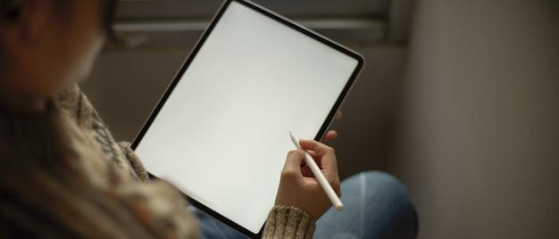読書コーナーに座っている間スタイラスペンで空白の画面垂直タブレットを使用して若い大学生の女の子