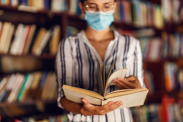 Молодая девушка колледжа с маской для лица стоит в библиотеке и держит книгу во время пандемии короны.
