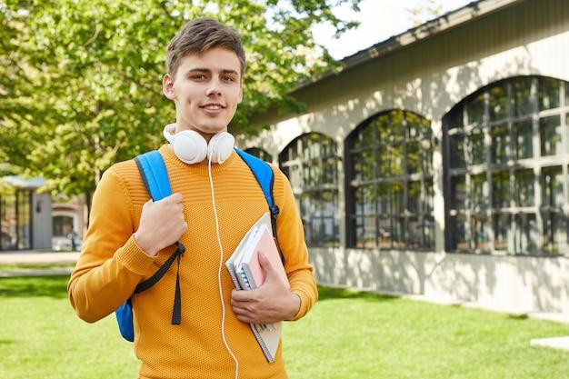 屋外でポーズ若い大学生