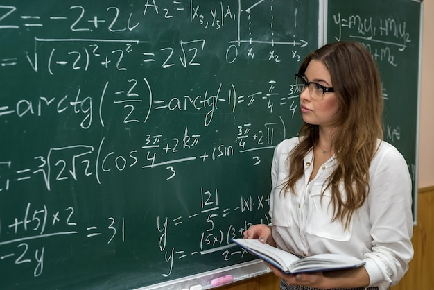 Young college student writing mathematical exercise on the chalkboard during a class. education