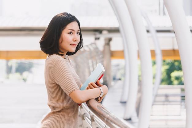Молодая женщина колледжа, держа книгу и ходить в кампусе