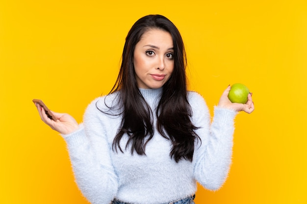 Young colombian girl having doubts while taking a chocolate tablet in one hand and an apple in the other
