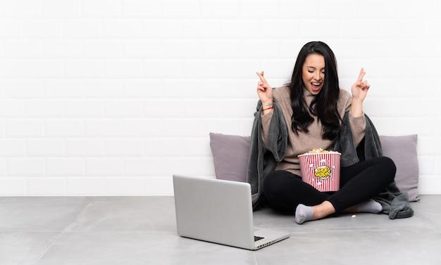 Молодая колумбийская девушка держит миску попкорна и показывает фильм в ноутбуке со скрещенными пальцами