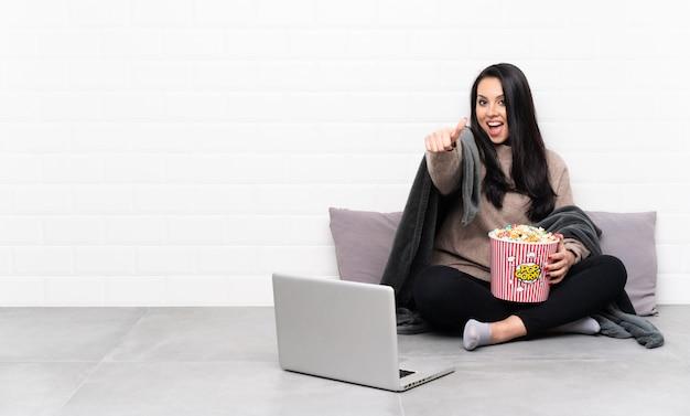 Молодая колумбийская девушка держит миску попкорна и показывает фильм в ноутбуке с пальцами вверх, потому что случилось что-то хорошее