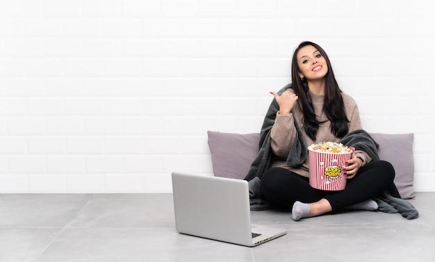 Молодая колумбийская девушка держит миску попкорна и показывает фильм в ноутбуке с недурно жестом и улыбкой