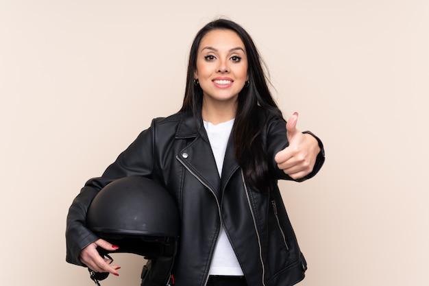 親指ジェスチャーを与える壁にオートバイのヘルメットを保持しているコロンビアの少女