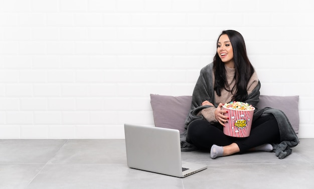Young colombian girl holding a bowl of popcorns and showing a film in a laptop happy and smiling