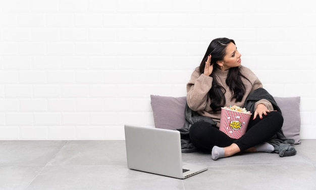 Young colombian girl holding a bowl of popcorns and showing a film in a laptop listening to something by putting hand on the ear