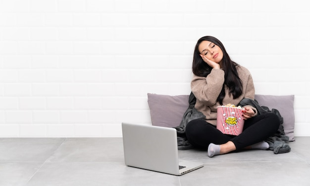 Young colombian girl holding a bowl of popcorns and showing a film in a laptop making sleep gesture in dorable expression