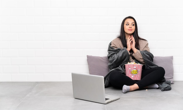 Young colombian girl holding a bowl of popcorns and showing a film in a laptop scheming something