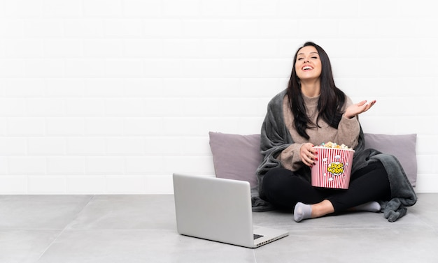 Young colombian girl holding a bowl of popcorns and showing a film in a laptop smiling a lot