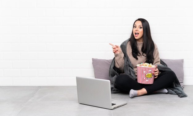 Young colombian girl holding a bowl of popcorns and showing a film in a laptop surprised and pointing finger to the side