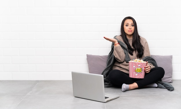 Young colombian girl holding a bowl of popcorns and showing a film in a laptop unhappy for not understand something