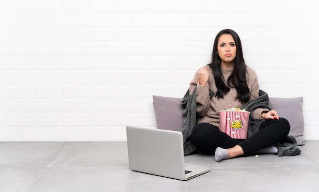 Young colombian girl holding a bowl of popcorns and showing a film in a laptop with angry gesture