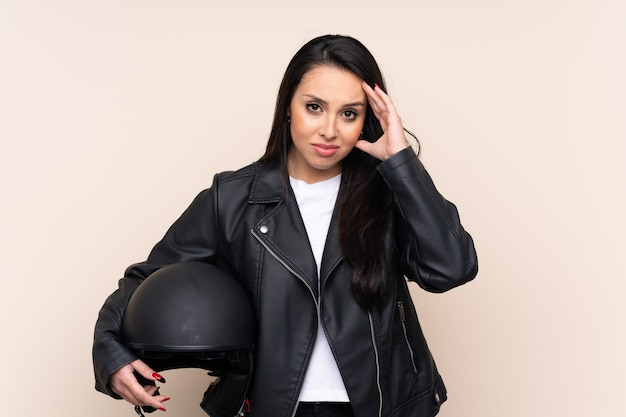 Young colombian girl holding a motorcycle helmet over wall unhappy and frustrated with something. negative facial expression