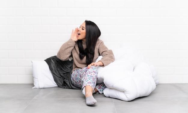 Молодая колумбийская девушка в пижаме в помещении кричит с широко открытым ртом к боковой