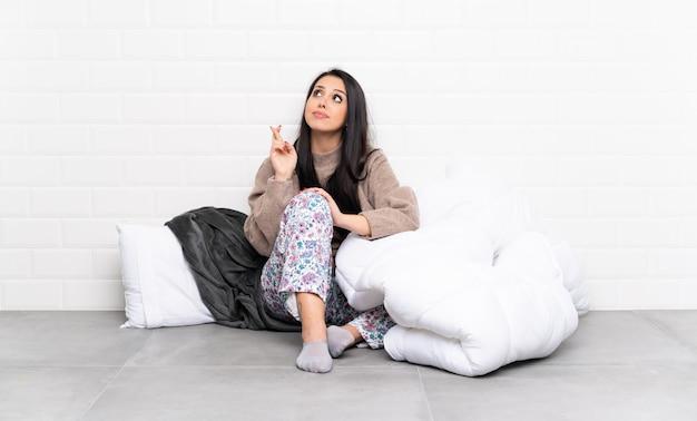 パジャマを着て屋内で指を交差し、最高を願ってコロンビアの少女