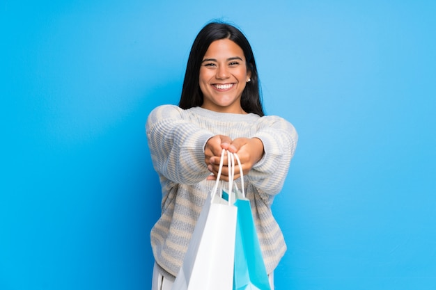 Young colombian girl with sweater holding a lot of shopping bags