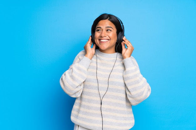 Young colombian girl with sweater listening to music with headphones
