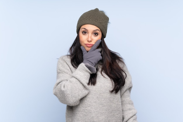 Young colombian girl with winter hat over blue wall thinking an idea
