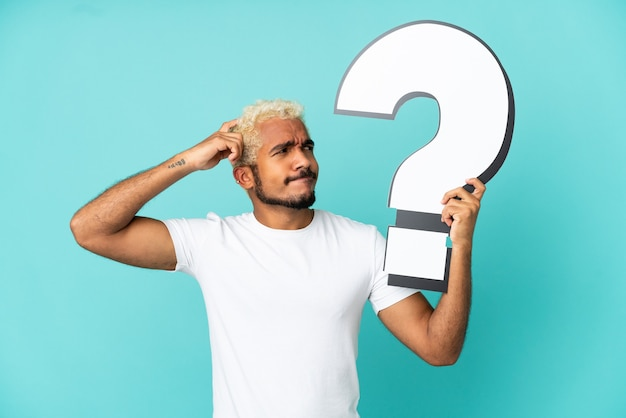 Young colombian handsome man isolated on blue background holding a question mark icon and having doubts