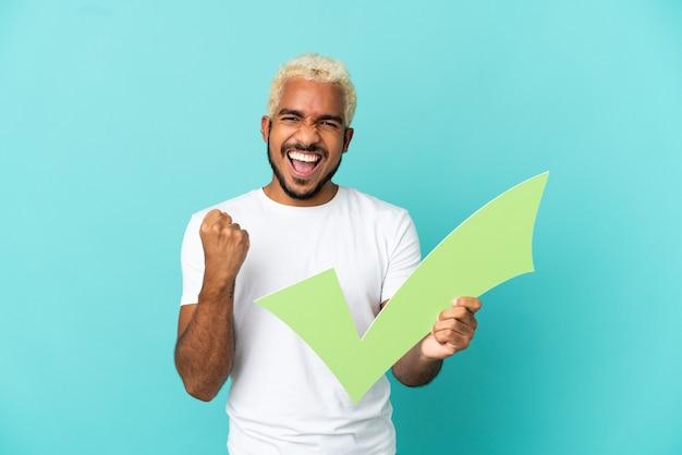 파란색 배경에 고립 된 젊은 콜롬비아 잘 생긴 남자는 수표 아이콘을 들고 승리를 축하