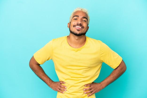 파란색 배경에 고립 된 젊은 콜롬비아 잘 생긴 남자 엉덩이에 팔을 포즈와 미소
