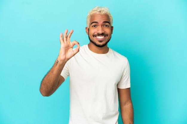 Молодой колумбийский красавец изолирован на синем фоне, показывая пальцами знак ок