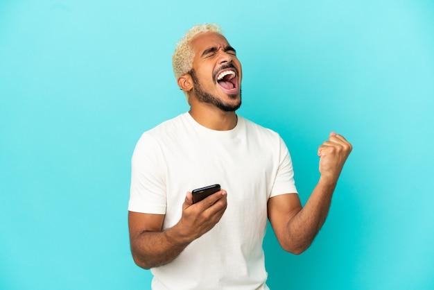 勝利の位置に電話で青い背景に分離された若いコロンビアのハンサムな男