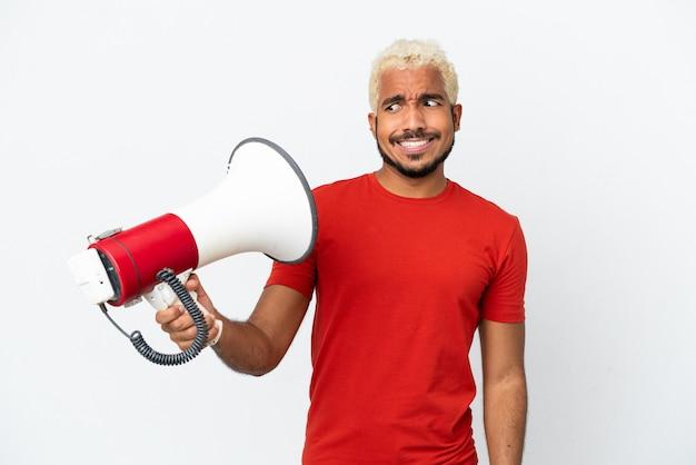 Молодой колумбийский красавец, изолированные на белом фоне, держит мегафон с подчеркнутым выражением лица