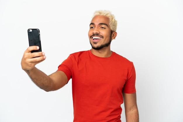 携帯電話でselfieを作る白い背景で隔離の若いコロンビアのハンサムな男
