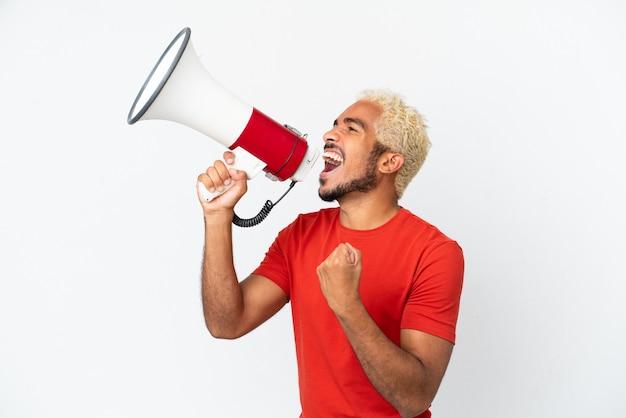 Молодой колумбийский красавец, изолированные на белом фоне, кричит в мегафон, чтобы объявить что-то в боковом положении Premium Фотографии
