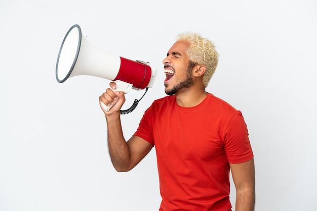 Молодой колумбийский красавец, изолированные на белом фоне, кричит в мегафон, чтобы объявить что-то в боковом положении