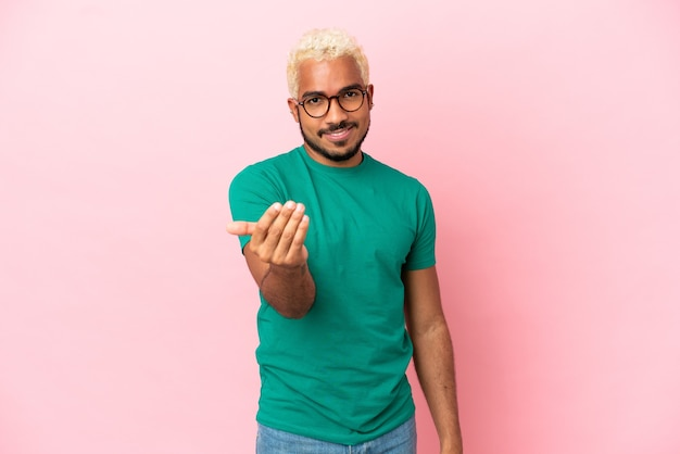 Young colombian handsome man isolated on pink background inviting to come with hand. happy that you came