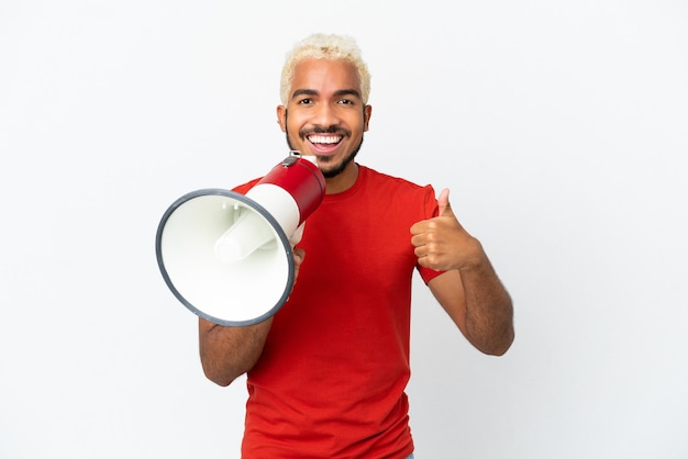 Young colombian handsome man isolated on white background shouting through a megaphone to announce something and with thumb up