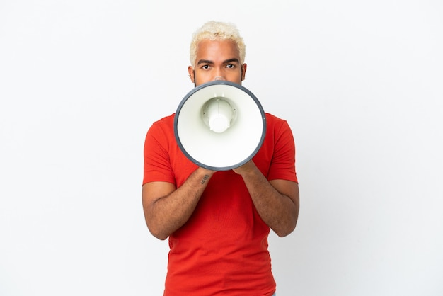 Young colombian handsome man isolated on white background shouting through a megaphone to announce something