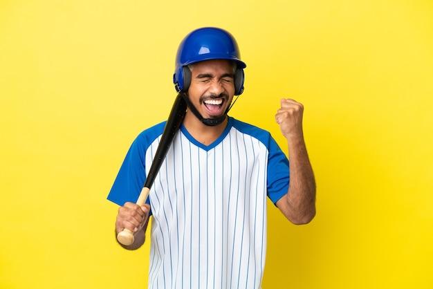Молодой колумбийский латинский мужчина играет в бейсбол на желтом фоне празднует победу Premium Фотографии