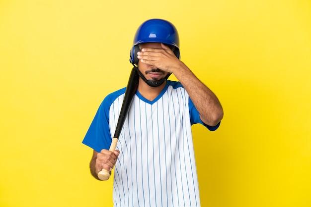 手で目を覆っている黄色の背景に分離された野球をしている若いコロンビアのラテン男性。何かを見たくない