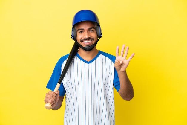 Молодой колумбийский латинский мужчина играет в бейсбол на желтом фоне счастлив и считает четыре пальцами