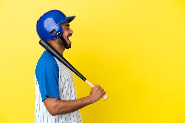 横の位置で笑って黄色の背景に分離された野球をしている若いコロンビアのラテン男性