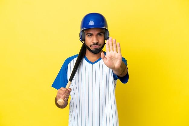 Молодой колумбийский латинский мужчина играет в бейсбол на желтом фоне, делая стоп-жест