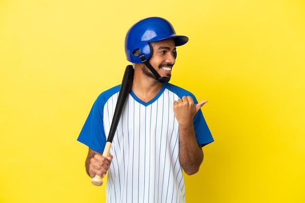 製品を提示する側を指している黄色の背景に分離された野球をしている若いコロンビアのラテン男性