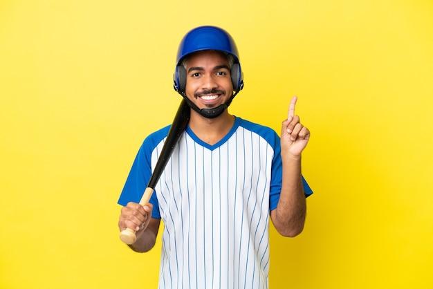 素晴らしいアイデアを指している黄色の背景に分離された野球をしている若いコロンビアのラテン男性