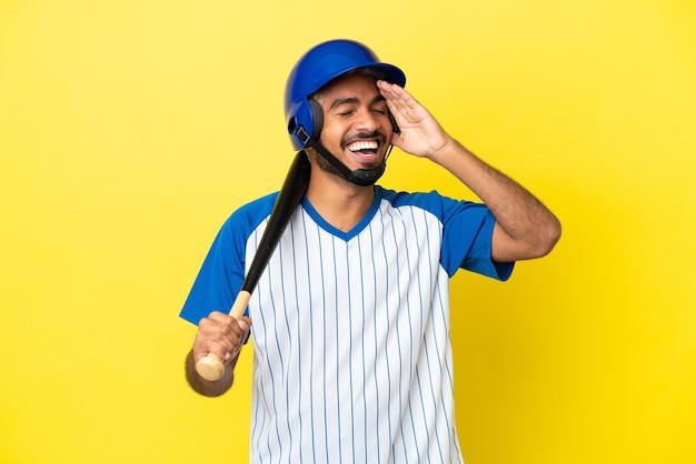 Молодой колумбийский латинский мужчина играет в бейсбол на желтом фоне, много улыбаясь
